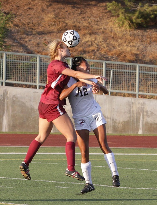 Benjamin Simpson / Courier Pasadena's Amanda Papac heads the ball forward over LA Pierce's Channise Bustamante during Pasadena's loss to LA Pierce College 0-1 at Robinson Stadium Sept 13, 2013.