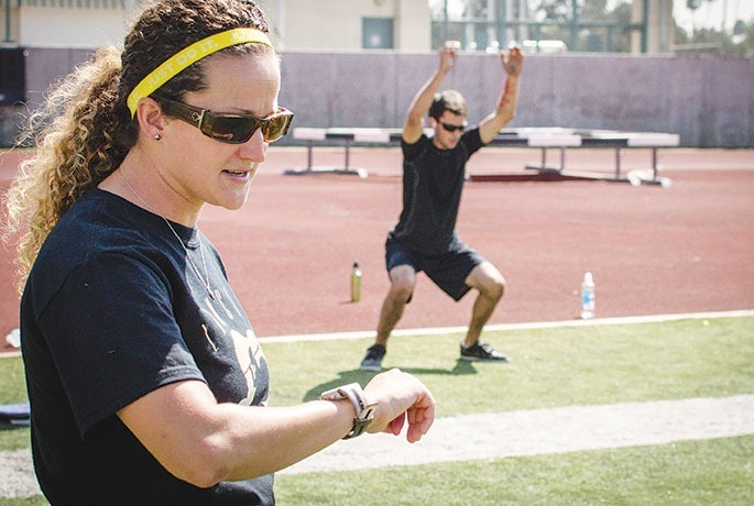 "Matthew Chan / Courier When she's not coaching, the new head coach of PCC""s softball team, Monica Tantlinger also teaches a cardiovascular conditioning class in Robinson Stadium, Sept. 19, 2013. Tantlinger keeps track of time as her students perform their conditioning drills."