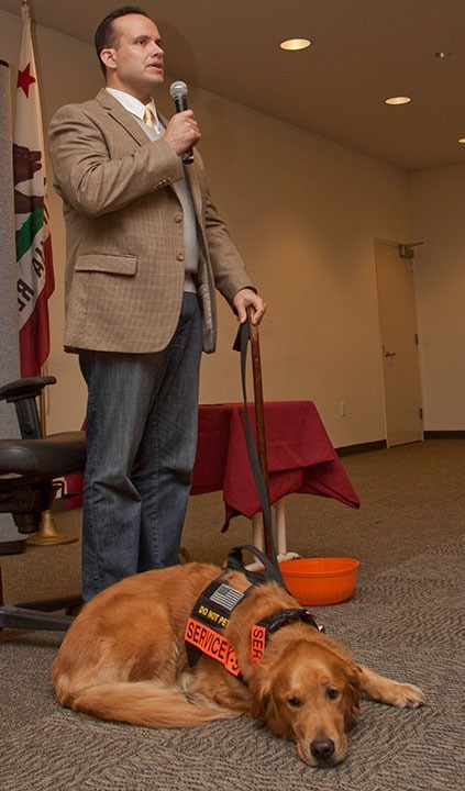 """Benjamin SImpson / Courier Luis Carlos Montalván, and his helper dog Tuesday, talk to students at the Creveling Lounge on Sept 17, 2013.  Montalván spoke about his 17 years in the military and his bestselling book 'Until Tuesday:  A Wounded Warrier and the Golden Retriever who Saved Him."""""""