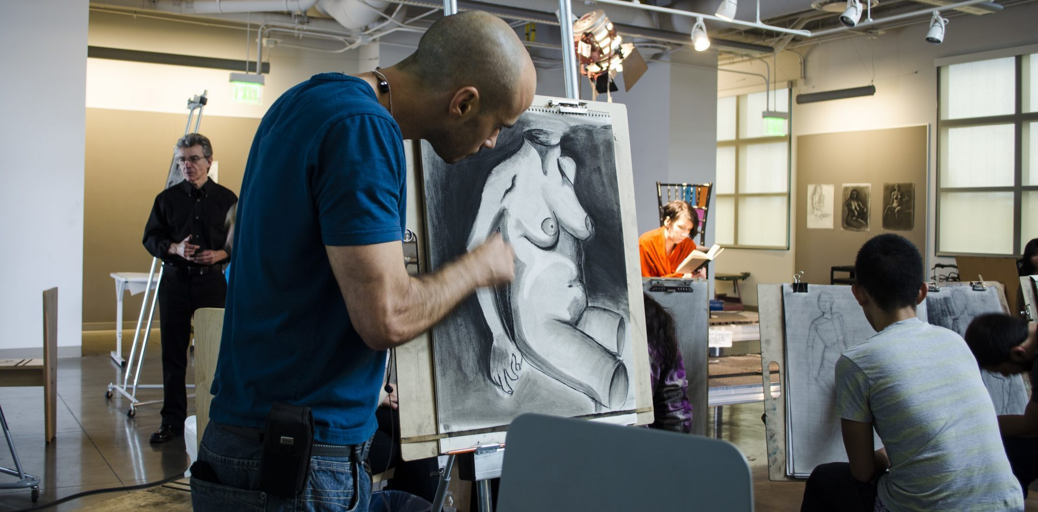 A student diligently works on a sketch of a nude model in the life drawing course.
