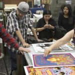 Katja Liebing/Courier  Dave Byrd discusses his artwork with screen printing students at Pasadena City College on Friday, April 15, 2016. Byrd worked for artists like Prince and the Rolling Stones.
